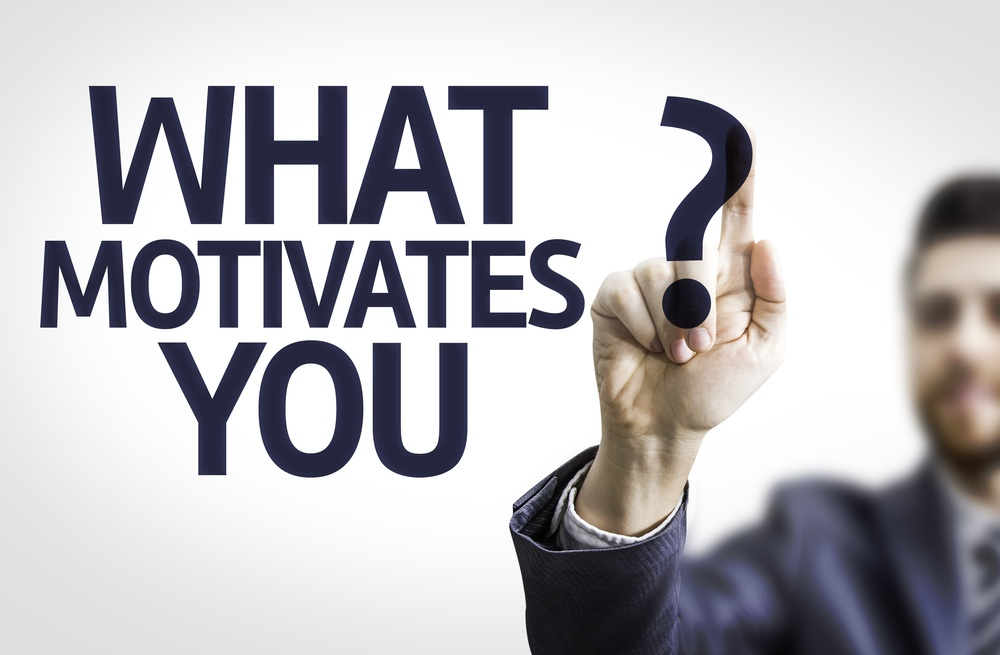 Business man pointing to transparent board with text What Motivates You?.jpeg